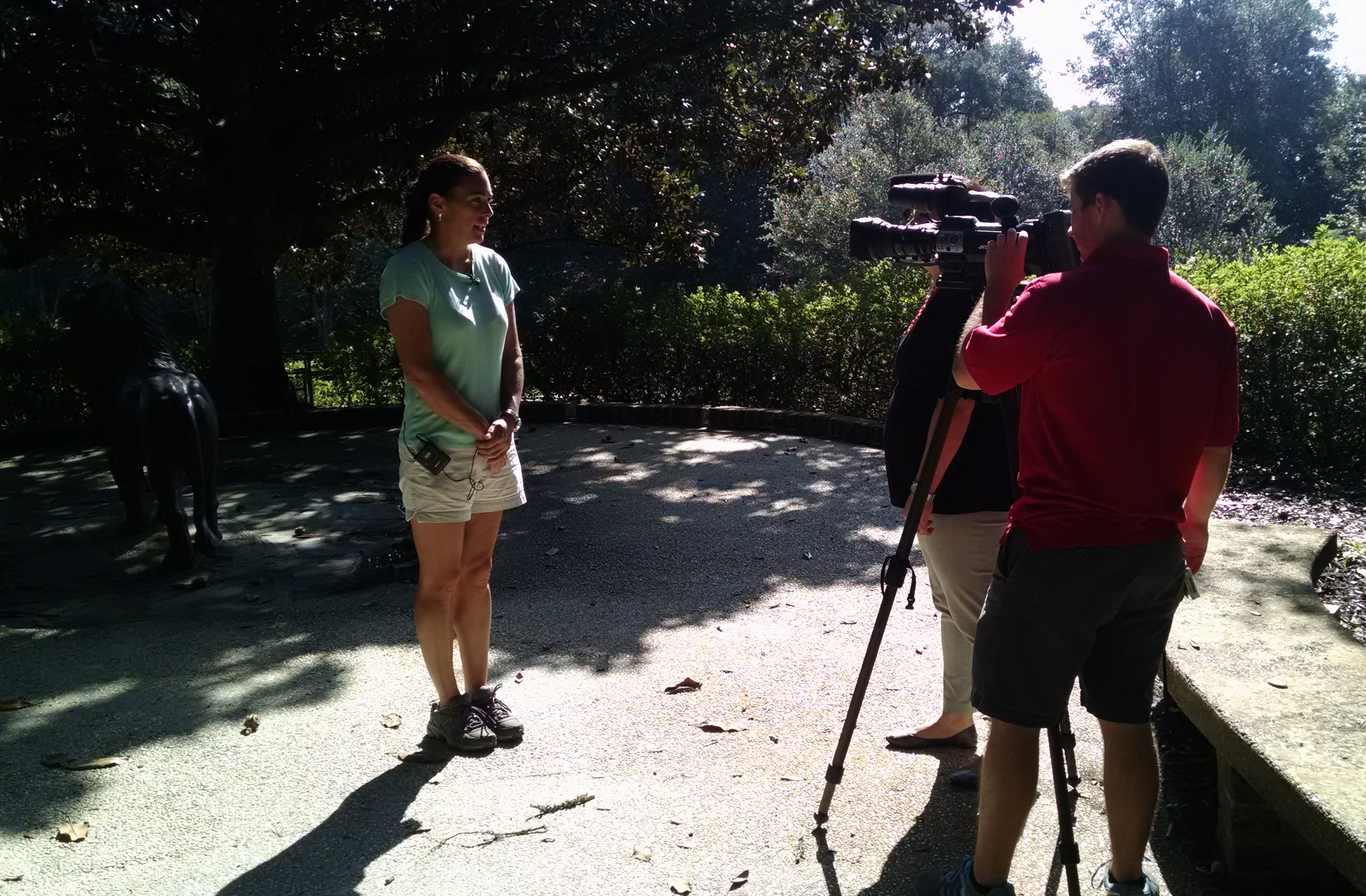 Melissa Wells, supervisor of Magic Christmas in Lights, talks with Katie Herrera and Stephen Smith of Local 15 WPMI on Sept. 8, 2015, as the Bellingrath crew hangs lights on one of the paths along Mirror Lake.